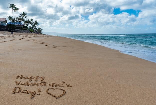 Joyeuse saint valentin avec un coeur dessiné dans le sable sur la plage