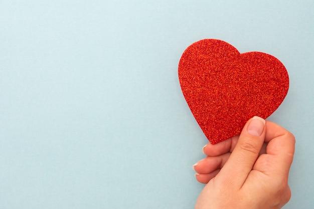 Joyeuse saint valentin. femme tenant un coeur rouge sur fond bleu, espace copie.