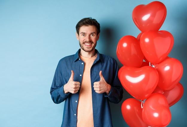 Joyeuse saint valentin. joyeux petit ami montrant les pouces vers le haut en approbation, debout avec des ballons coeurs rouges pour amant, fond bleu.