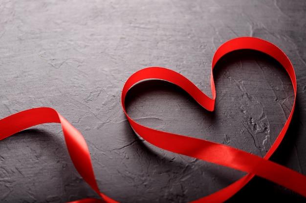 Joyeuse saint valentin. ruban rouge sur fond de pierre noire. concept de la saint-valentin