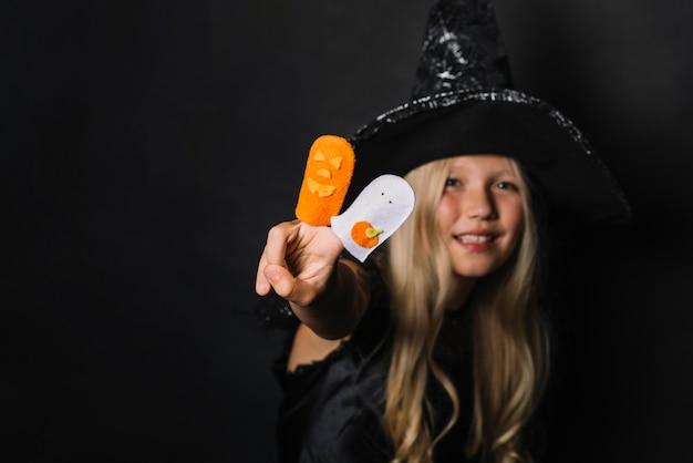 Joyeuse sorcière gesticulant victoire avec des jouets d'halloween