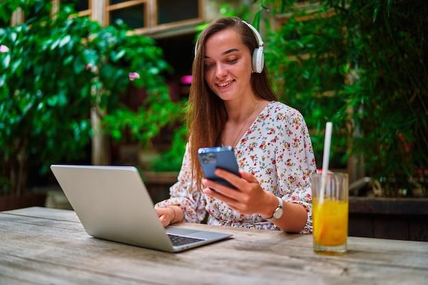 Joyeuse souriante belle jeune fille indépendante du millénaire portant des écouteurs sans fil utilisant un ordinateur portable et un téléphone pour le travail à distance, les réseaux sociaux et la navigation en ligne au café vert