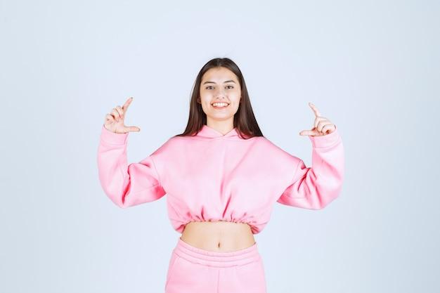 Joyeuse vendeuse en pyjama rose faisant la promotion de quelque chose avec confident sur la scène