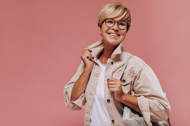 Joyeuse vieille dame avec une coiffure courte blonde et une peau bronzée en veste moderne beige souriant et tenant un sac frais sur fond isolé.