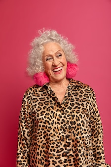 Joyeuse vieille femme aime la vie, sourit largement, a des dents blanches parfaites, regarde avec une expression joyeuse de côté, porte des boucles d'oreilles moelleuses et une robe léopard, se souvient de sa jeunesse, se souvient de quelque chose de très agréable