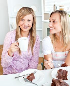 Joyeuses amies mangeant un gâteau au chocolat et boire dans la cuisine