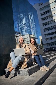 Joyeuses amies avec des ordinateurs portables assis sur les marches de la rue