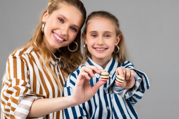 Joyeuses belles dames présentant de minuscules hamburgers dans leurs mains tout en souriant agréablement