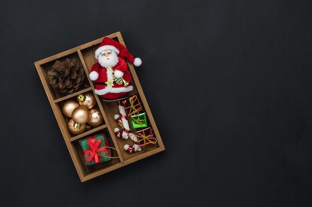 Joyeuses décorations de noël. boîte cadeau d'objets de différence essentielle à plat et sapin sur papier noir moderne