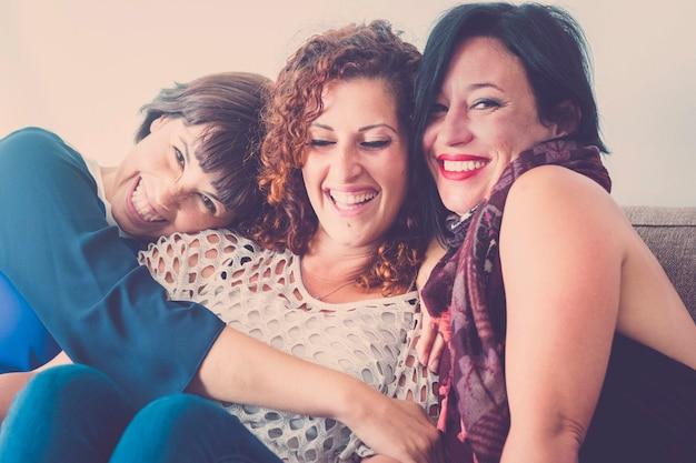 Joyeuses femmes d'âge moyen young womane amis ensemble assis sur un canapé à la maison dans l'activité de loisirs à l'intérieur