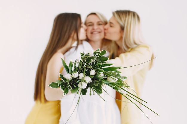 Joyeuses femmes blondes de deux générations isolées sur fond blanc. bouquet de fleurs.