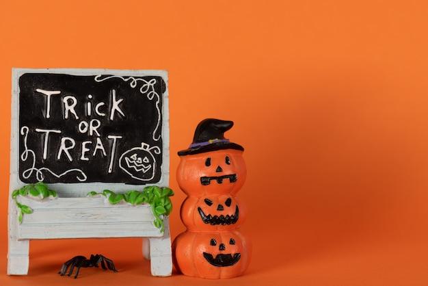 Joyeuses fêtes d'halloween, trick or treat avec citrouilles et araignées sur orange