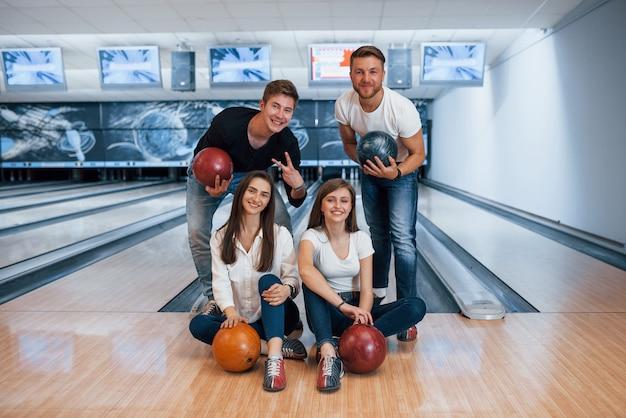 Joyeuses fêtes. de jeunes amis joyeux s'amusent au club de bowling le week-end