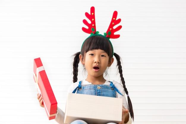 Joyeuses fêtes et noël enthousiaste mignonne petite fille tenant sa boîte cadeau au salon blanc.