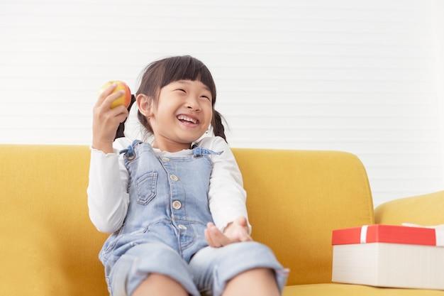 Joyeuses filles mignonnes pour enfants mangent une pomme près du cadeau actuel