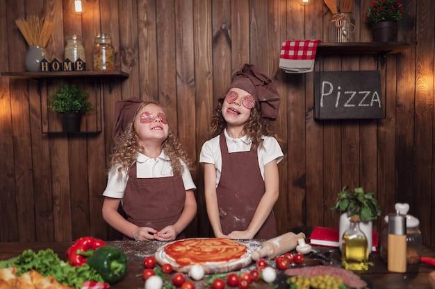Joyeuses filles s'amusant avec des saucisses dans la cuisine