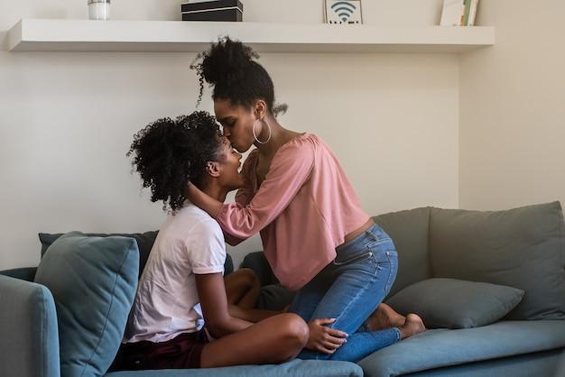 Joyeuses jeunes copines étreignant et embrassant sur le canapé à la maison
