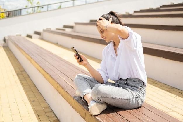 Joyeuses jeunes femmes gaies avec un smartphone profitant d'une journée ensoleillée assise dans l'amphithéâtre