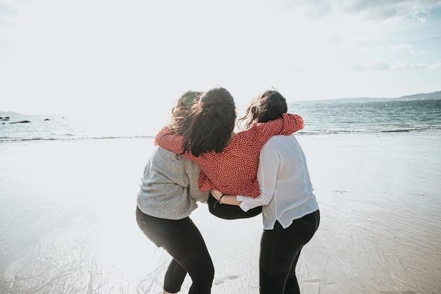 Joyeuses jeunes femmes riant et souriant à la plage un jour d'été, profitant de vacances, concept d'amitié profitant de l'extérieur