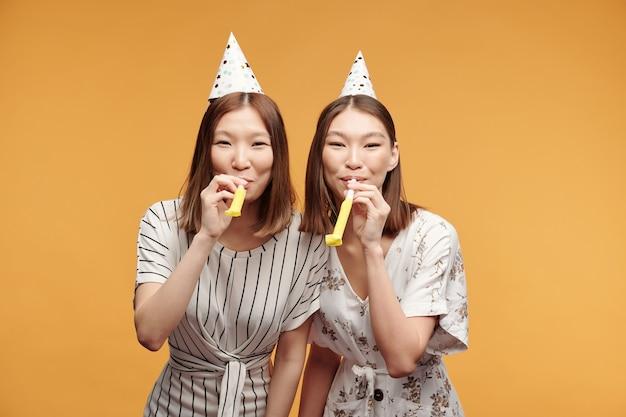 Joyeuses jeunes jumelles asiatiques dans des vêtements décontractés intelligents et des casquettes d'anniversaire vous regardant tout en sifflant devant la caméra