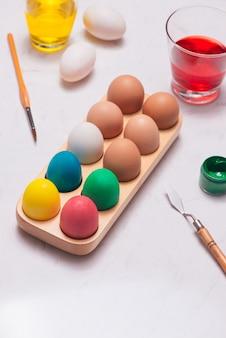 Joyeuses pâques! amis peignant des oeufs de pâques sur la table.