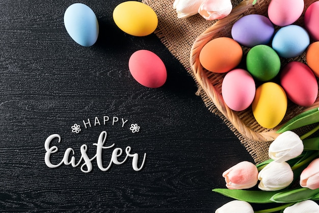 Joyeuses pâques! coloré d'oeufs de pâques dans son nid avec des tulipes flowe
