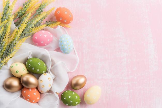 Joyeuses pâques! coloré des oeufs de pâques en nid avec fleur sur fond rose.