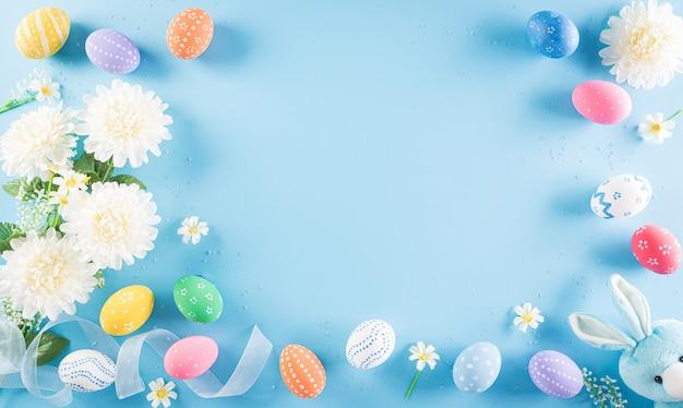 Joyeuses pâques colorées d'oeufs de pâques avec des fleurs sur fond bleu pastel.