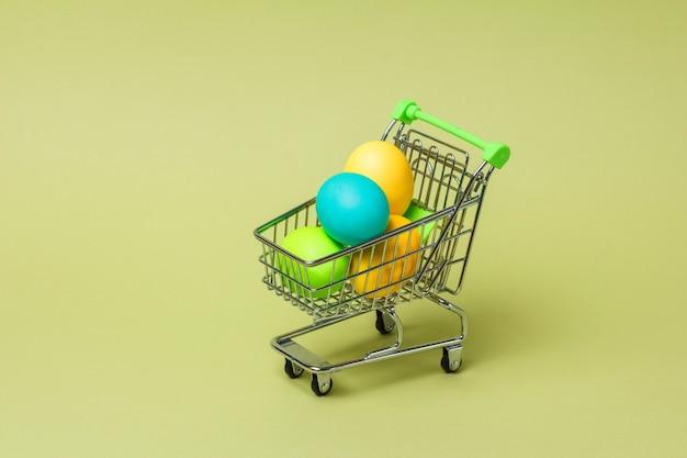 Joyeuses pâques concept avec des oeufs de pâques dans le chariot de supermarché