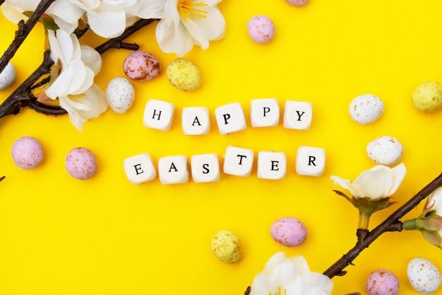 Joyeuses pâques. cubes avec texte sur fond jaune. brunchs de printemps avec des fleurs blanches et des bonbons, des oeufs de pâques au chocolat. mise à plat minimaliste.