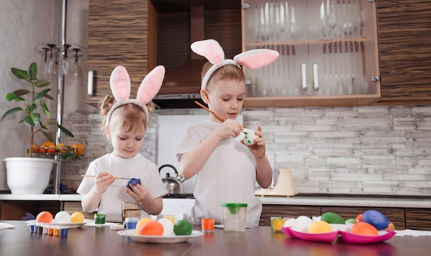 Joyeuses pâques. enfants drôles et heureux un garçon et une fille avec des oreilles de lapin jouent, se préparent pour les vacances et peignent des œufs.