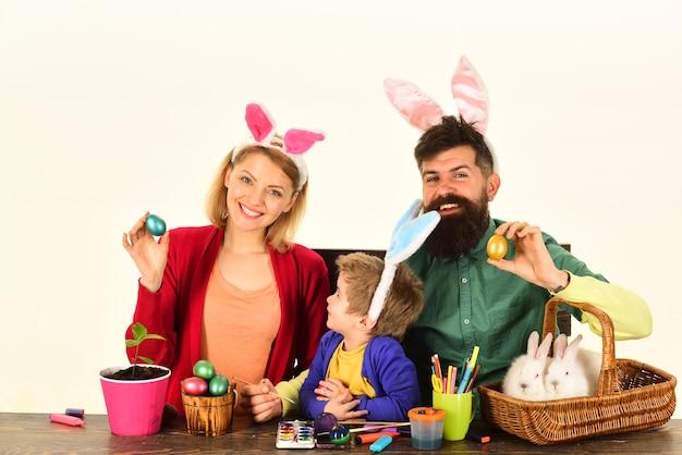 Joyeuses pâques! fond blanc isolé. mère, père et enfant peignant des œufs de pâques. lapin de famille d'oeufs de pâques avec des oreilles de lapin drôles.