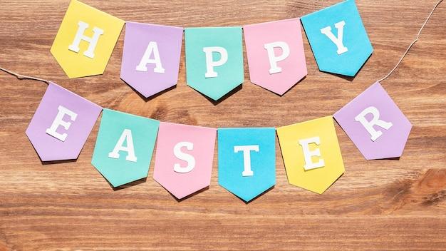 Joyeuses pâques fond avec des drapeaux en papier colorés sur bois