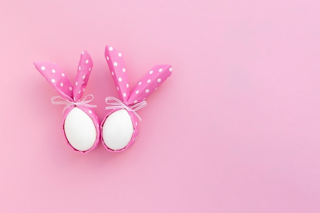 Joyeuses pâques fond festif. deux oeufs de pâques avec des oreilles de lapin sur rose avec espace de copie.