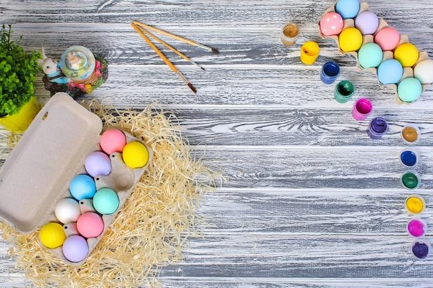 Joyeuses pâques. fond avec des oeufs colorés dans le panier. décoration de table pour les vacances. vue de dessus.