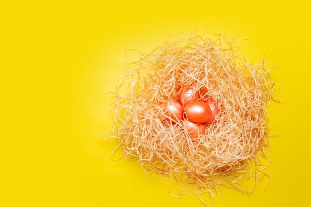 Joyeuses pâques fond, oeufs de couleur rose et orange dans le nid de foin sur la couleur jaune vif