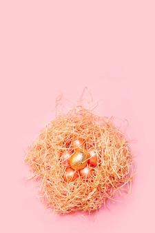 Joyeuses pâques fond, oeufs roses et dorés colorés dans un nid de foin sur une couleur rose vif