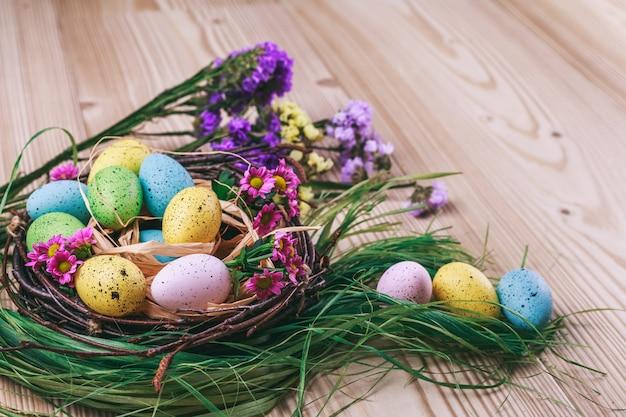 Joyeuses pâques. fond de pâques. œufs colorés dans un nid avec des fleurs de printemps sur fond sombre en bois