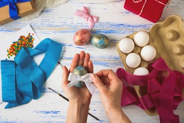 Joyeuses pâques. des mains féminines peignent et décorent des oeufs de pâques sur une table en bois