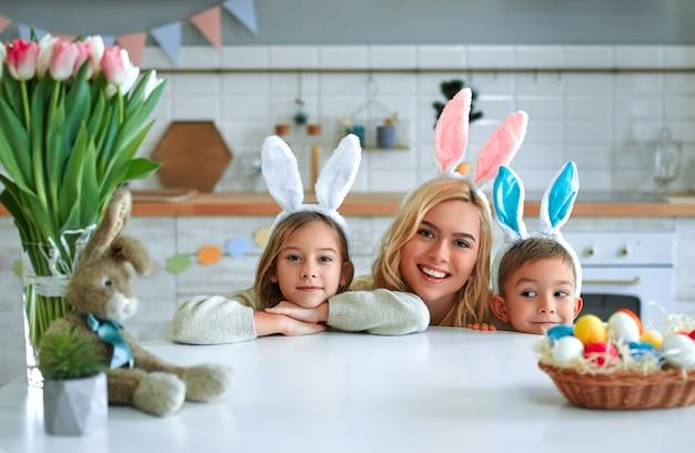 Joyeuses pâques! mère, fils et fille commencent à chasser les œufs de pâques. héhé, préparation pour pâques. mignon petit garçon et fille portant des oreilles de lapin le jour de pâques.
