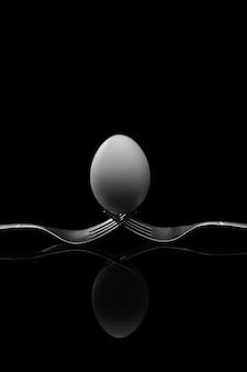 Joyeuses pâques, oeuf blanc deux fourchettes argent antique sur fond noir