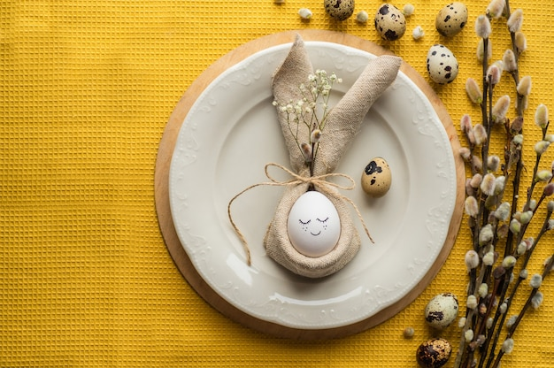 Joyeuses pâques. oeuf mignon dans une serviette en forme de lapin sur une assiette en céramique.