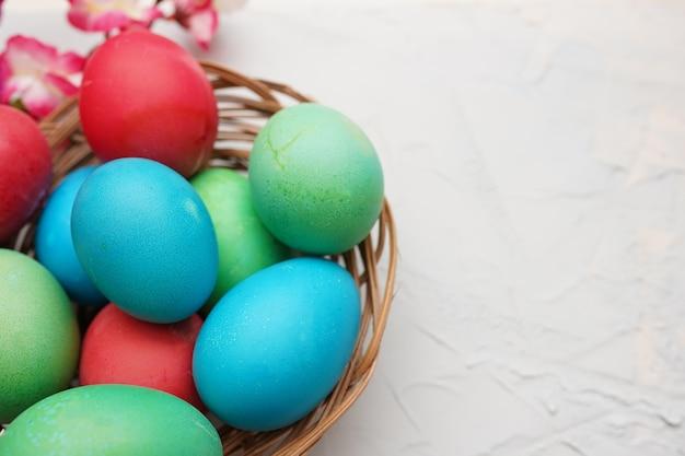 Joyeuses pâques - oeufs bleus et rouges colorés dans le panier