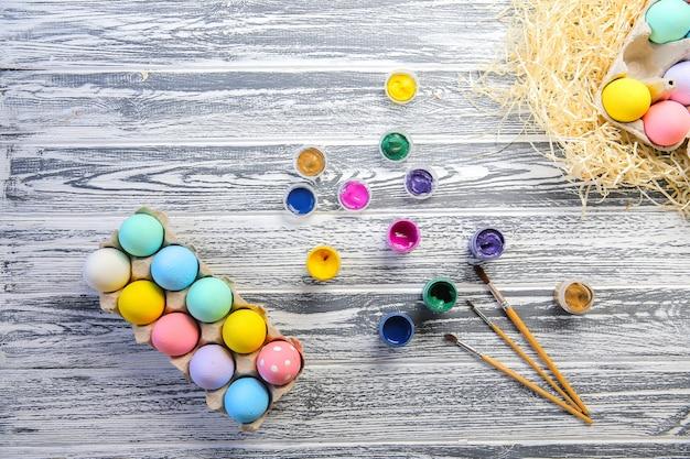 Joyeuses pâques. oeufs colorés dans le panier. décoration de table pour les vacances. vue de dessus.