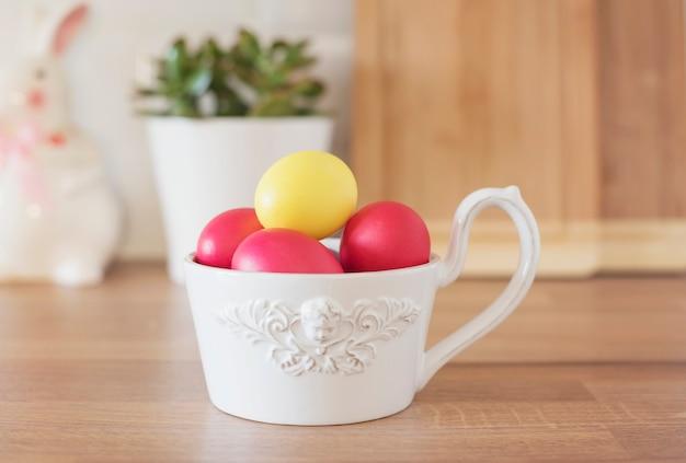 Joyeuses pâques! oeufs de pâques colorés dans un bol blanc, lapin, succulentes sur le comptoir de la cuisine, gros plan. ustensiles de cuisine à l'intérieur de la cuisine moderne.
