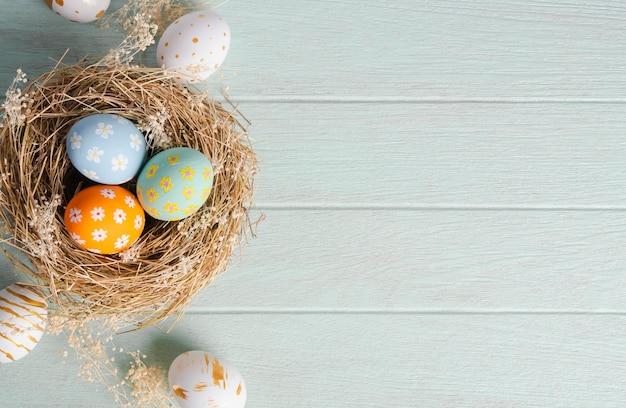 Joyeuses pâques, oeufs de pâques peints au nid sur une table rustique en bois pour votre décoration en vacances. vue de dessus avec espace copie.