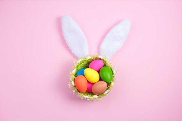 Joyeuses pâques avec des oreilles de lapin adorables sur un panier rempli d'oeufs de pâques sur fond rose