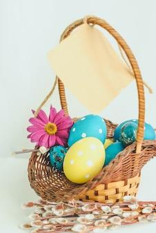 Joyeuses pâques panier en osier plein d'oeufs peints colorés et papier suspendu sur fond blanc