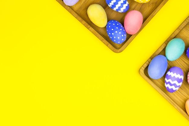 Joyeuses pâques plaques en bois en forme de coeur, carré avec oeufs de pâques colorés avec visage comique sur fond jaune