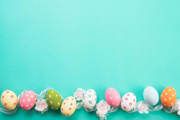 Joyeuses pâques! rangée d'oeufs de pâques sur fond pastel vert.
